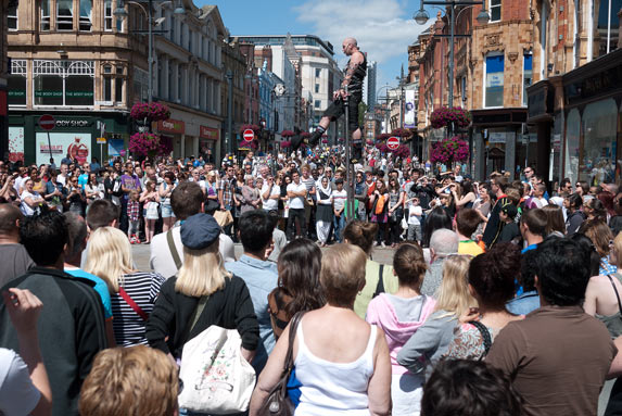 crowd in Leeds city center watching a street performer