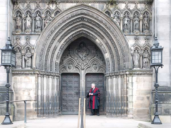 ecclesiastic standing by the door of St Giles Cathedral in Edinburgh