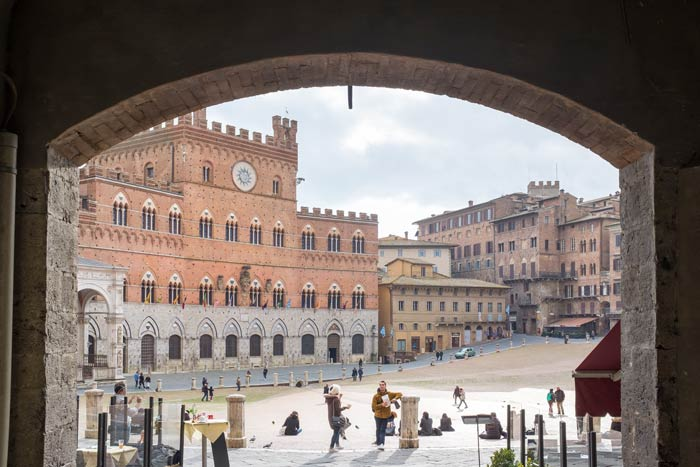 View through an archway looking out at el Campo in Siena