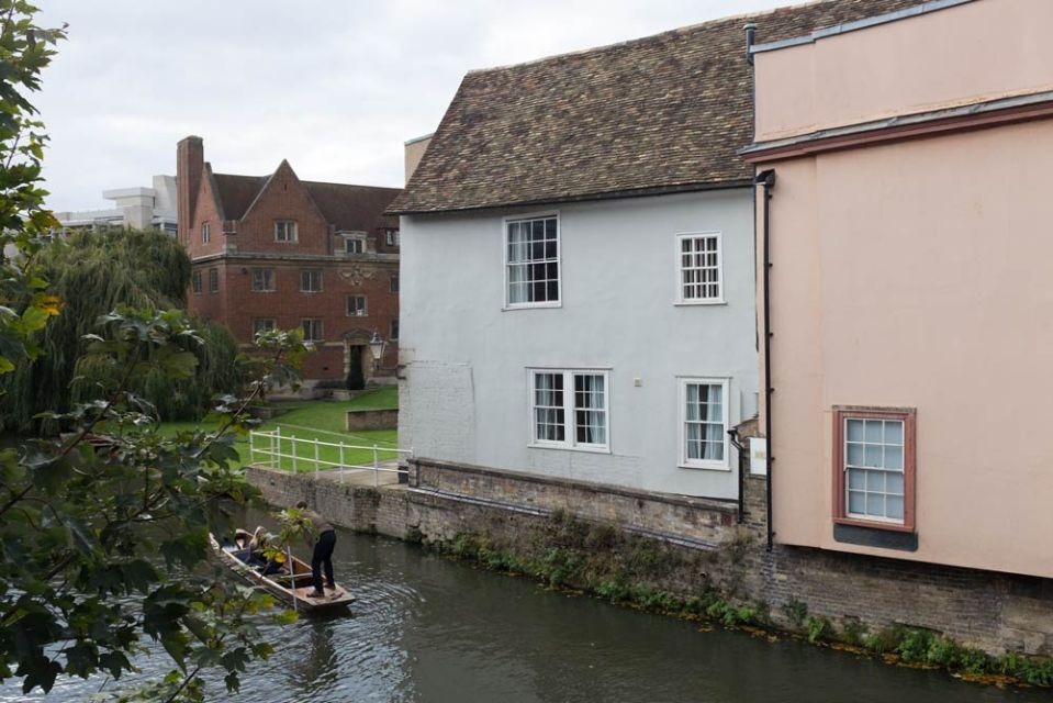Pastel-coloured buildings and a punt on the river Cam in Cambridge, England