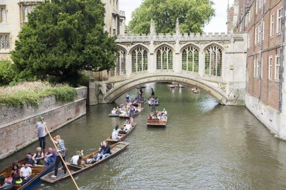 Rush hour for punts on the river Cam that threads itself below the Bridge of Sighs at St. John's College, Cambridge
