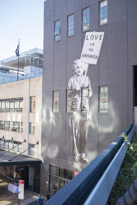 Mural of Einstein holding a poster 'Love Is The Answer' from the High Line in New York