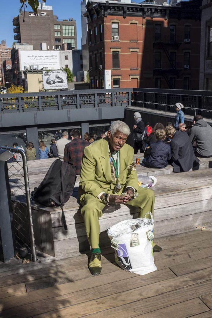 man in a green suit sitting on a wall on the high line in New York