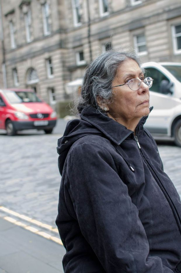 candid street photography on the streets of Edinburgh - woman sitting and resting on a bollard - properly processed shot