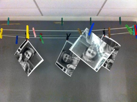 film prints drying, hung on pegs in the darkroom