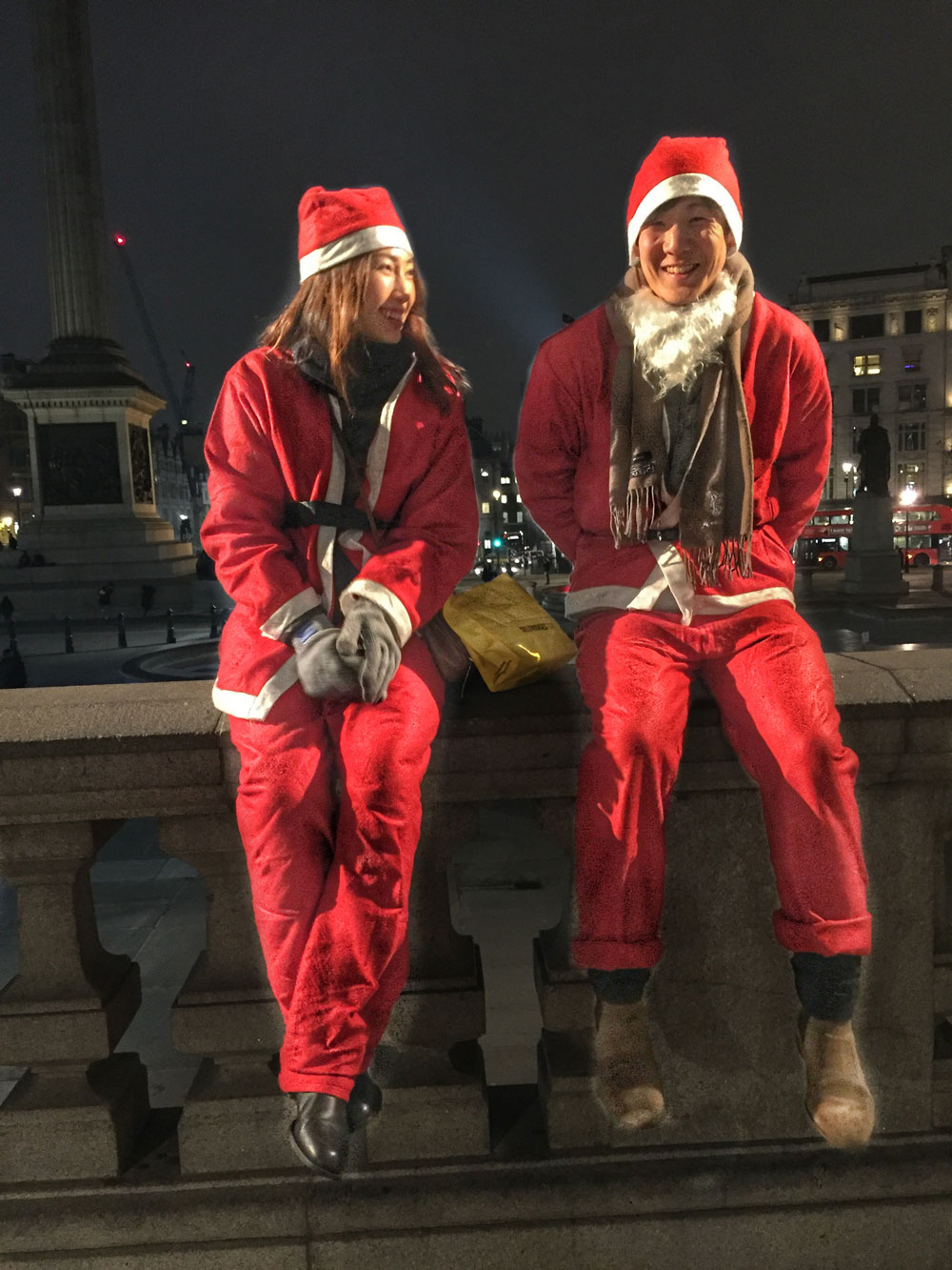 couple in father Christmas outfits sitting on a wall at Trafalgar Square in London