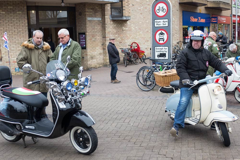 vespa scooters - and riders talking - and one setting off