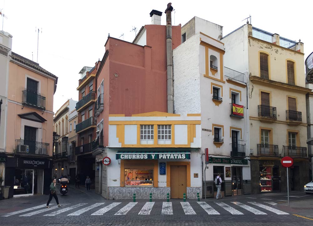 street scene in Spain with shop selling churros y patatas