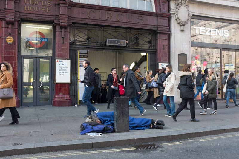 Man sleeping rough outside an exit to Oxford Circus tube station during the Extinction Rebellion protest in London