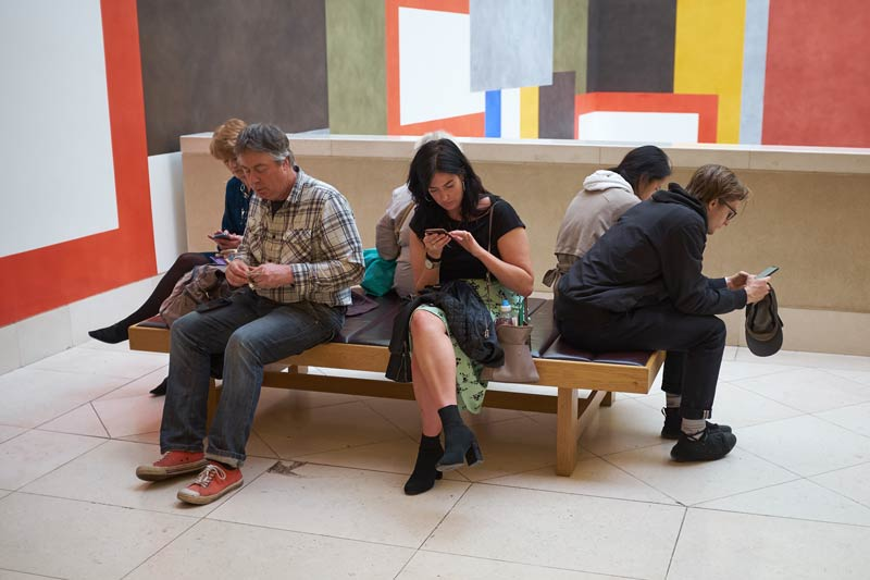people on a bench at the Tate Britain in London -  all on their phones - modern life