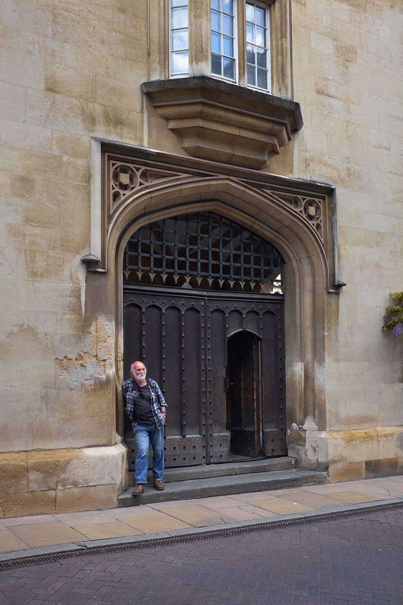 Man leaning against the doorway of Sidney Sussex College in Cambridge