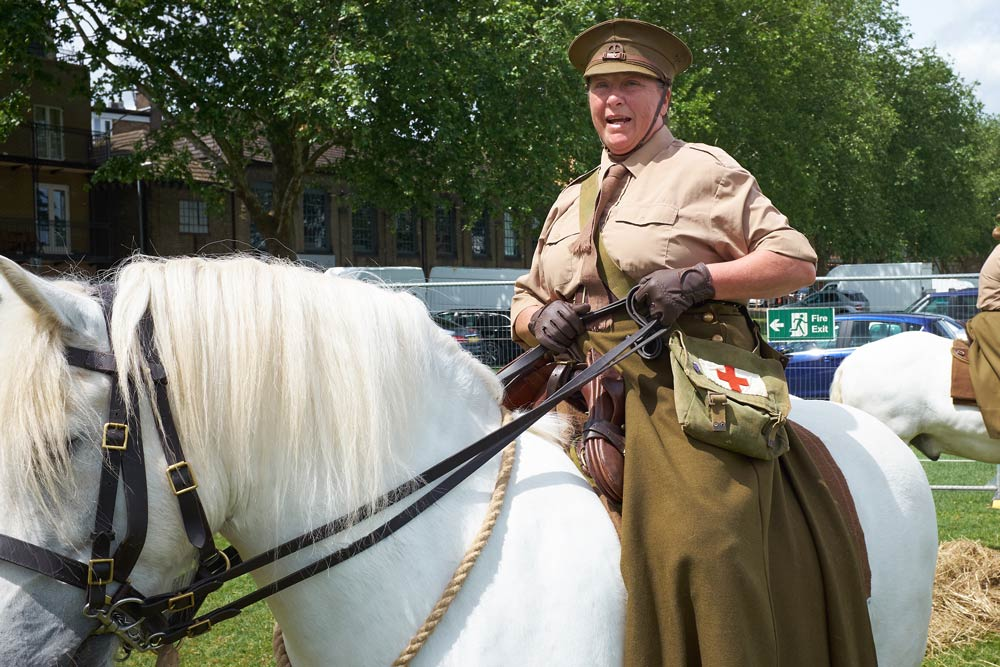 White Highland pony ridder by a woman who is a member of the First Aid Nursing Yeomanry (FANY)