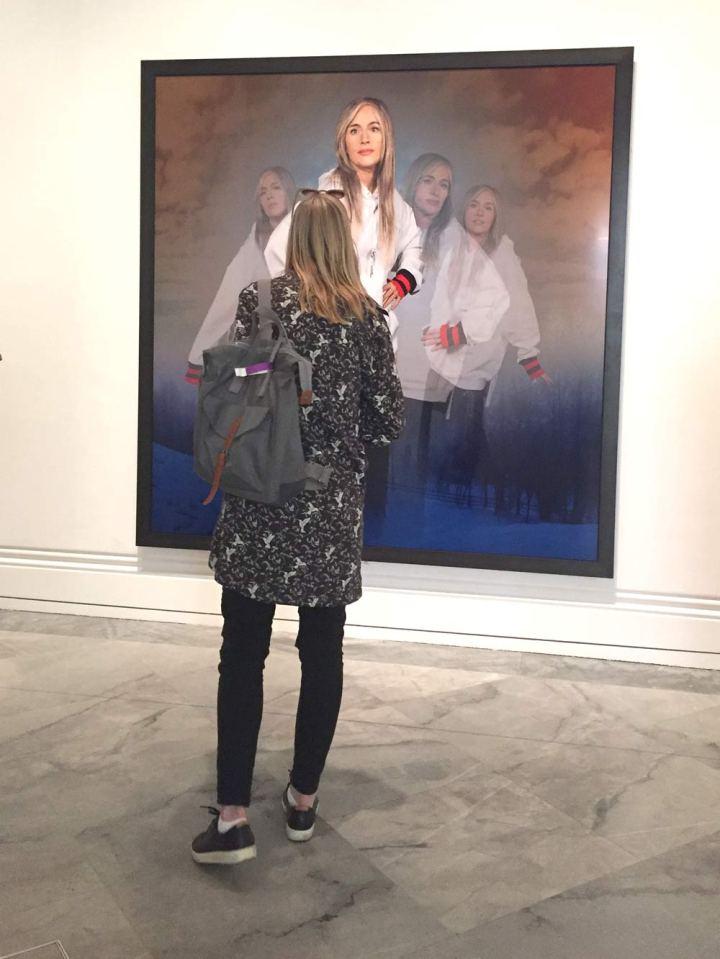 Young woman looking at a Cindy Sherman photograph.