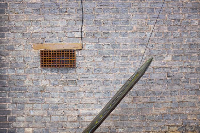 A ventilation grate, some wires or cables, a piece of wood at an angle, and everything against a brick wall.