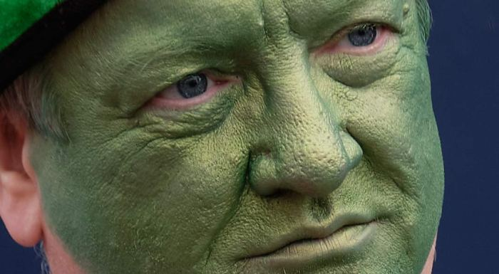 Man with green face lost in thought
