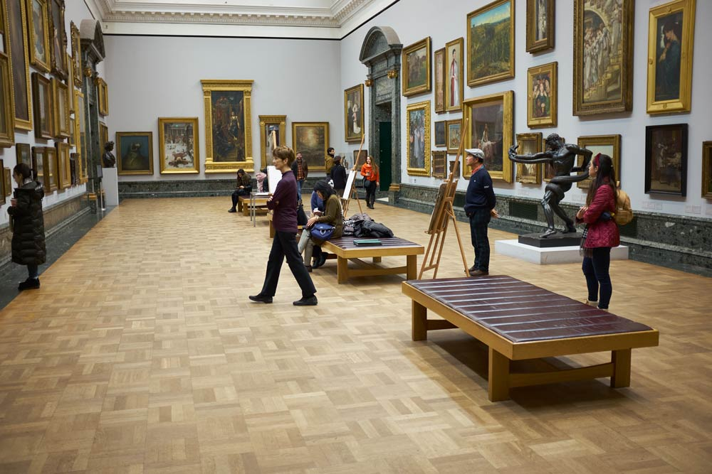 A room of paintings in Tate Britain with sketch easels and people looking at the paintings