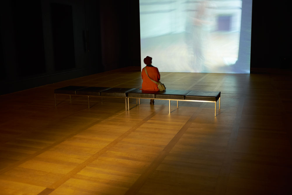 Woman sitting alone in a room in Tate Britain, watching a film in near darkness