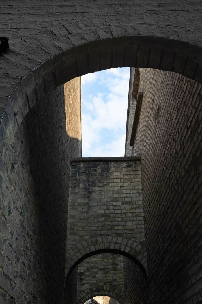 near wall darkened to illustrate Photoshop capabilities to set mood is a street scene showing a patch of blue sky above enclosed arches and walls in Cambridge