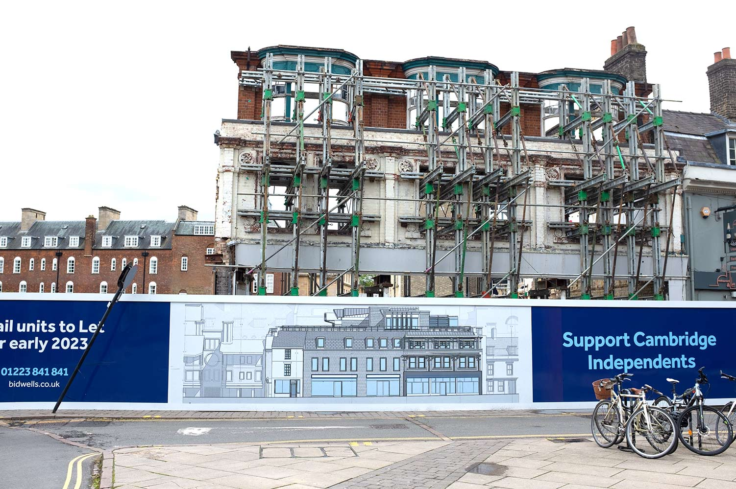 facade of a newly demolished building fronted by the architect's impression of what the new development with look like